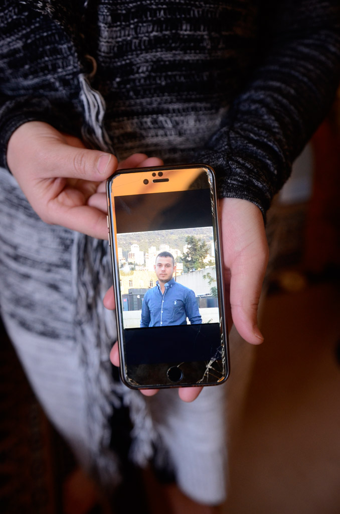 Ammar's mother holds a photo of her son on her phone, an image that would bring her comfort during the separation.